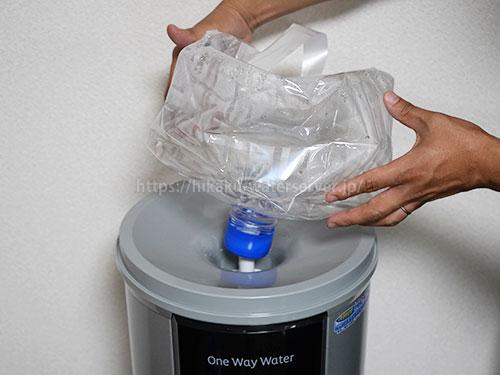 ワンウェイウォーター「スタイリッシュウォーターサーバー」の使用済みボトルをサーバーから取り外している写真